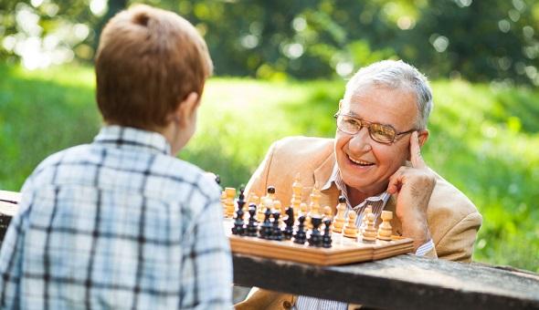 Opa und Enkel spielen zusammen Schach