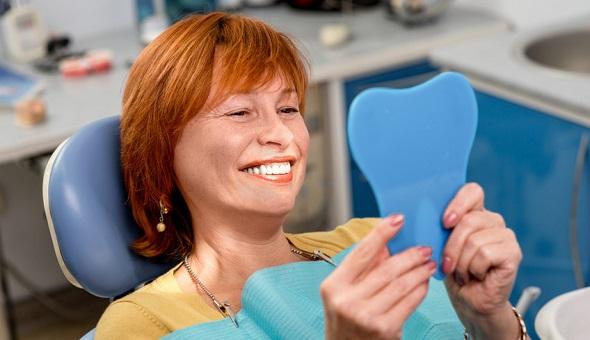 Diese Frau ist zufrieden mit ihrer Entscheidung für einen Zahnersatz.