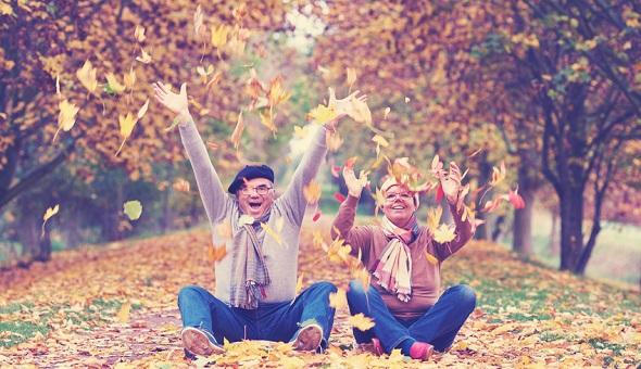 Zwei Senioren sitzen im Herbstlaub und schmeißen es lachend in die Luft.
