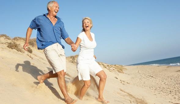 Ein Mann und eine Frau laufen glücklich am Strand.