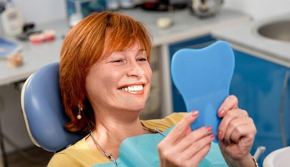 Eine Frau sieht sich in einer Zahnarztpraxis ihre Zähne in einem Spiegel an.