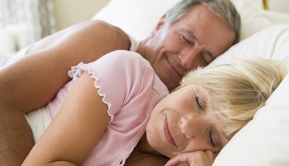 Eine Frau und ein Mann liegen im Bett und schlafen.