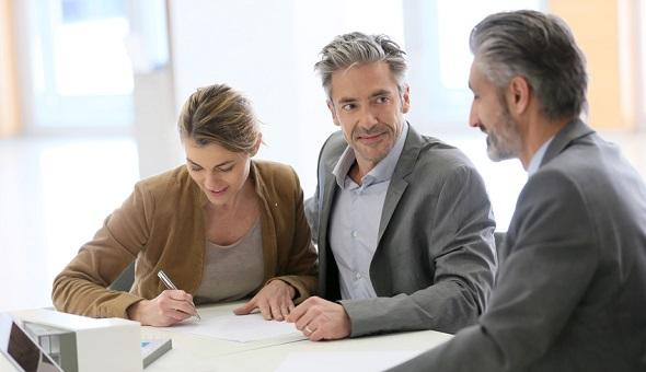 Eine Frau und zwei Männer sitzen in einem Büro am Tisch und lächeln.