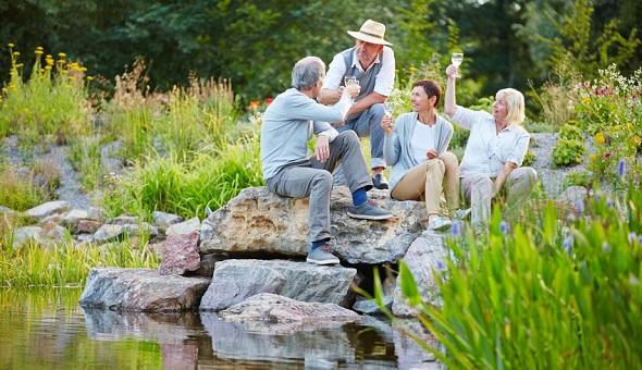 Glückliche Senioren feiern gemeinsam Geburtstag mit Sekt im Garten