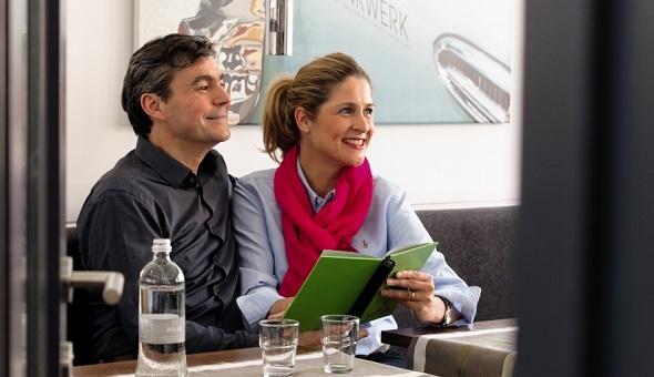 Ein Mann und eine Frau sitzen im Restaurant und betrachten die Speisekarte.