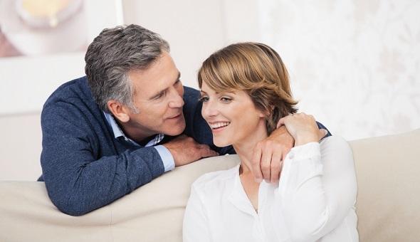 Ein Mann und eine Frau sitzen gemeinsam auf einem Sofa.