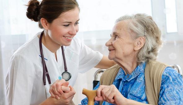 Eine frau im höheren Alter und eine Pflegefachkraft lächeln sich an.