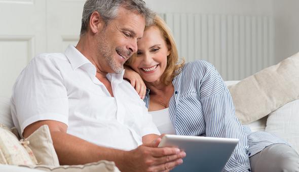 Ehepaar auf dem Sofa mit Senioren-Tablet.