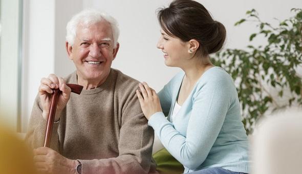Eine junge Frau und ein Mann höheren Alters sitzen gemeinsam auf einem Sofa.