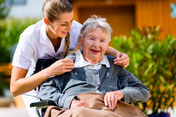 Tagespflege: Pflegerin kümmert sich um Senioren im Rollstuhl.