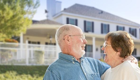 Ein älteres Ehepaar lächelt glücklich in die Kamera.