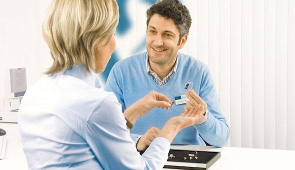 Hörakustiker berät eine Frau bezüglich der Wahl des richtigen Hörgeräts.